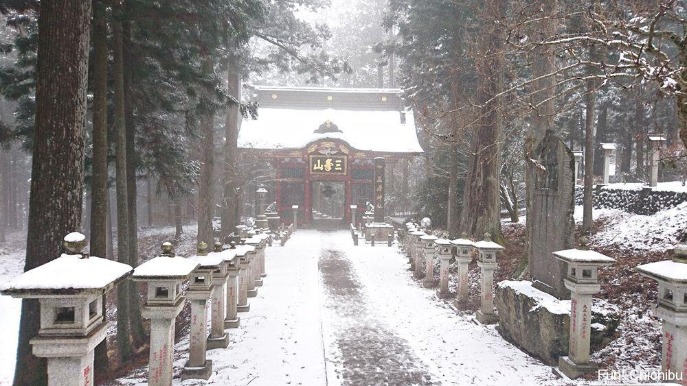 雪の中の隋身門を遠くから見る